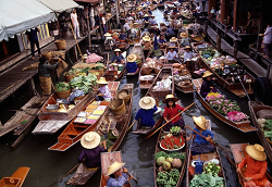 Row boats selling vivid color fruits are a feature of Damneon Saduak floating market