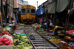 merchants are moving back their awnings and shop fronts to let the train pass at Mae Klong Railway Market
